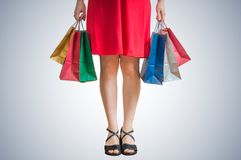 Legs of shopping woman holding many colorful bags in hands.  stock photography