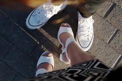 Legs on a sidewalk tile. Close-up of girls legs on a sidewalk tile Royalty Free Stock Image