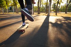 The legs of a skateboarder girl in sneakers do a trick on a skateboard. Royalty Free Stock Photography