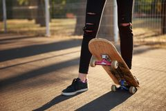 The legs of a skateboarder girl in sneakers do a trick on a skateboard. Stock Image