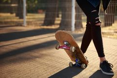 The legs of a skateboarder girl in sneakers do a trick on a skateboard. Royalty Free Stock Image