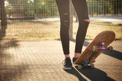 The legs of a skateboarder girl in sneakers do a trick on a skateboard. Royalty Free Stock Photos