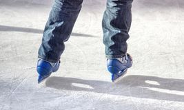 Ice skater with blue skates. Legs of a skater with blue skates on ice Royalty Free Stock Photos