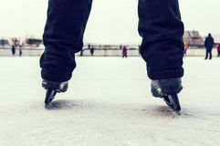 Legs of skater in motion at skating rink. Legs in black ice skating pants with back view. Winter outdoor activities Stock Photography
