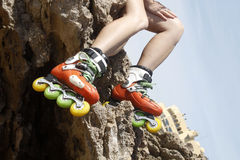 Legs with skates in a rock and a building. In Cascais, Lisbon, Portugal Stock Photos
