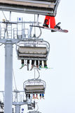 Legs of skiers and snowboarders riding on a cable chair lift in cloudy snowy winter mountains scenic vertical close up Stock Photography