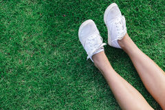 Legs in skirt and white slip-ons in the grass with copyspace Stock Image