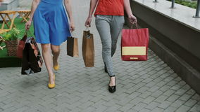 Legs slender young women walking down the street past the store with shopping bags, slow mo stedicam shot. Legs slender young women friends, walking in the city stock footage