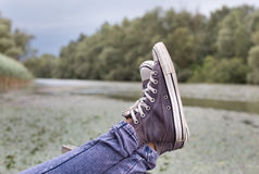 Legs with sneakers on the lake Stock Image