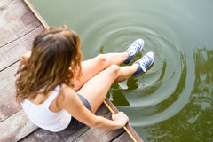 Legs in sneakers making circles in a water Royalty Free Stock Photo