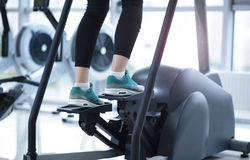Legs in sneakers running on a treadmill Royalty Free Stock Photography