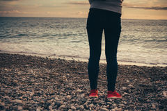 Legs and sneakers on the sea beach. Royalty Free Stock Image