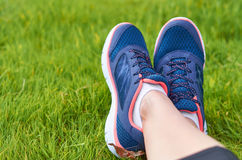 Legs with sneakers sports girls on a green lawn. The concept of leisure and sports Royalty Free Stock Photography