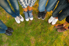 Legs and sneakers of teenage boys and girls. Standing in half circle on the grass Stock Images