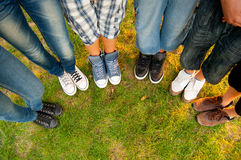 Legs and sneakers of teenage boys and girls. Standing in half circle on the grass Stock Photography