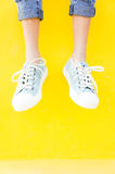 Legs sneakers on yellow background, lifestyle fashion Royalty Free Stock Images