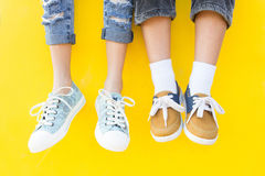 Legs sneakers on yellow background, lifestyle fashion Stock Photo