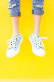 The Legs sneakers on yellow background, lifestyle fashion Royalty Free Stock Photography
