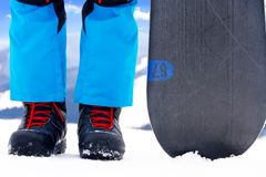 Legs in snowboarder boots with snowboard Royalty Free Stock Images