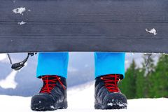 Legs in snowboarder boots with snowboard Stock Photo