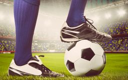 Legs of a soccer or football player. On ball on stadium, warm colors toned Stock Photos
