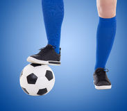Legs of soccer player and ball close-up over blue Stock Images
