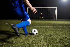 Soccer player making a kick towards the goal. Legs of a soccer player about to kick off the soccer ball from the green grassy sports field towards the goalpost Royalty Free Stock Image