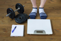Legs in socks standing in front of the weights on the floor. Legs in socks standing in front of weights Stock Photo