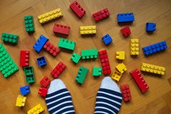Legs socks stripes white blue yellow red cubes constructions puzzle toys game floor wooden. Legs staying in socks stripes white blue yellow pink orange violet royalty free stock photo