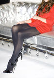 Legs on sofa. Sexy woman sitting in splendid shiny sofa with her black court shoes and red skirt Stock Image