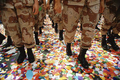 Legs of soldiers walking on confetti Royalty Free Stock Images