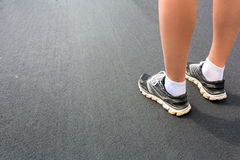 Legs in sport shoes on asphalt road closeup Royalty Free Stock Photos