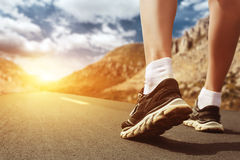 Legs in sport shoes on road at sunset closeup. Stock Photo