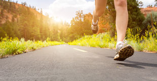 Legs in sport shoes on road at sunset closeup. Royalty Free Stock Photos