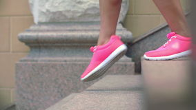 Legs in sport shoes walking down stairs in slow motion stock video