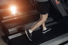 Legs of sportsman running on treadmill: sport and healthy lifestyle concept. Stock Images
