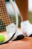 Legs of sportswoman near the tennis racket Royalty Free Stock Photos