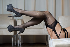 Legs with stockings, garter belt and high heels shoes Stock Images