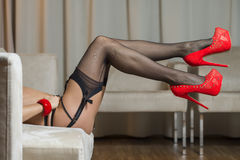 Legs with stockings, garter belt and red high heels shoes Royalty Free Stock Images
