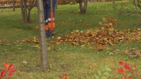 Legs of street cleaner who pile up leaves in park stock footage