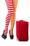 Legs in striped stockings and suitcase isolated on Stock Photo