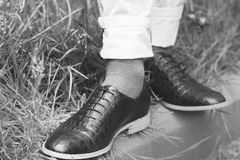 Legs in stylish shoes on grass. Greyscale Stock Photo