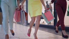 Legs of stylish shopper women rush on seasonal discounts in fashion boutique and carry lot of shopping packages