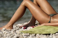 Legs in the Sun # 2. Dark skinned woman sunbathing on a pebble beach Stock Image