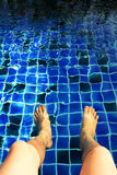 Legs in the swimming pool with blue tiles Royalty Free Stock Images