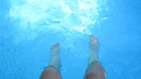 Legs in the swimming pool. Man is playing with his legs underwater in the swimming pool. Waving legs in the water stock video footage