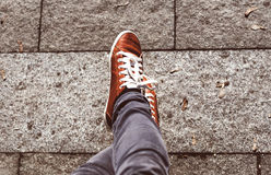 Legs of a teenager in jeans and sneakers. Legs of a teenager in jeans and sports shoes Royalty Free Stock Photos