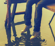 Legs of teenager sitting on the wooden dock Royalty Free Stock Photos
