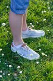 Legs of teenager standing on meadow on sunny spring day Stock Image