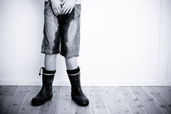Legs of teenager with wet pants and boots Stock Image